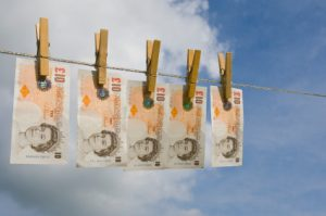 UK currency - new £10 notes - 'drying' on a washing line on a breezy Summer's day. Symbolising money laundering.